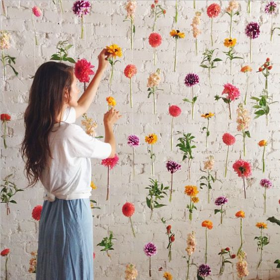 A woman decorating a white brick wall with colorful flowers that create a hanging flower backdrop