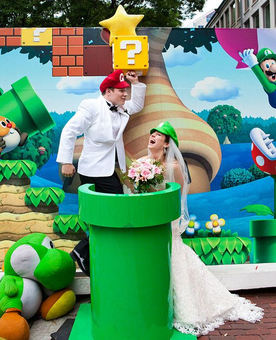 A Super Mario photo booth display with a wedding couple dressed as Mario and Luigi for a photo