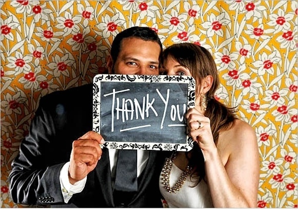 "wedding couple holding a board with ""thank you"" written on it"