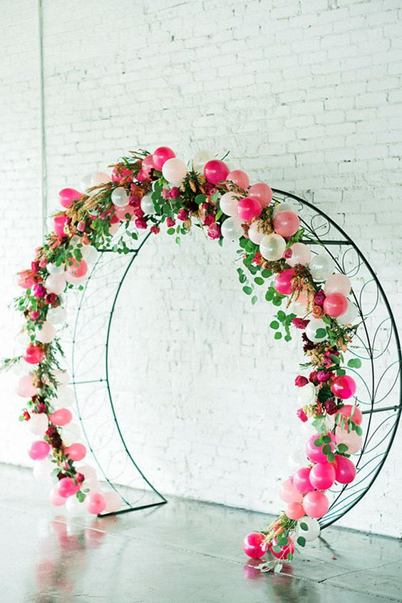 A circular wire arch decorated with bright pink and pastel pink flowers