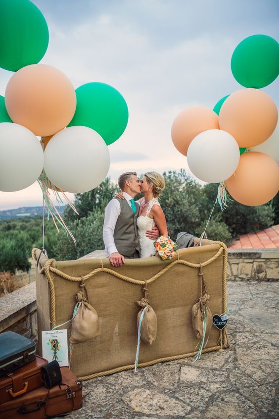 A pretend hot air balloon set-up for a photo booth with a basket for the wedding couple to stand in and giant helium balloons attached to the basket
