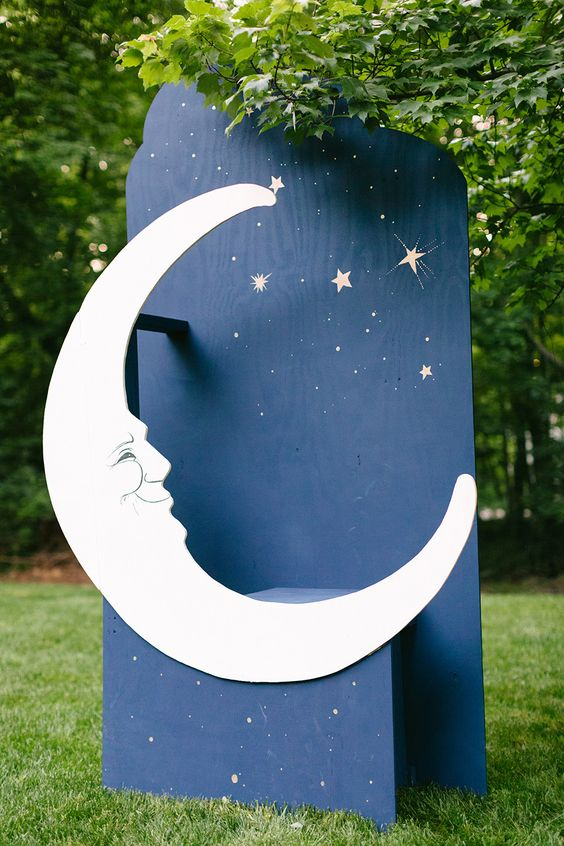 A giant moon attached to a standing blue backboard placed outside
