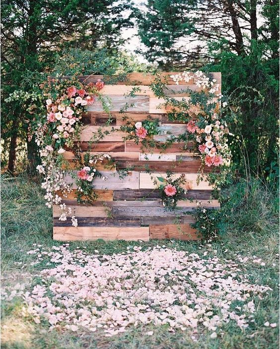 A standing display of wooden planks that create a background with fresh flowers draped over it