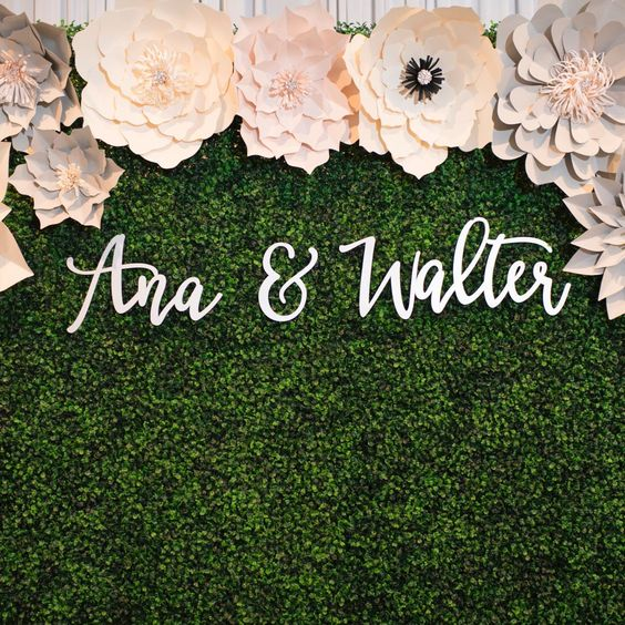 """A beautiful backdrop made up of large paper flowers against a green hedge, with the names """"Ana & Walter"""" displayed against the greenery"""