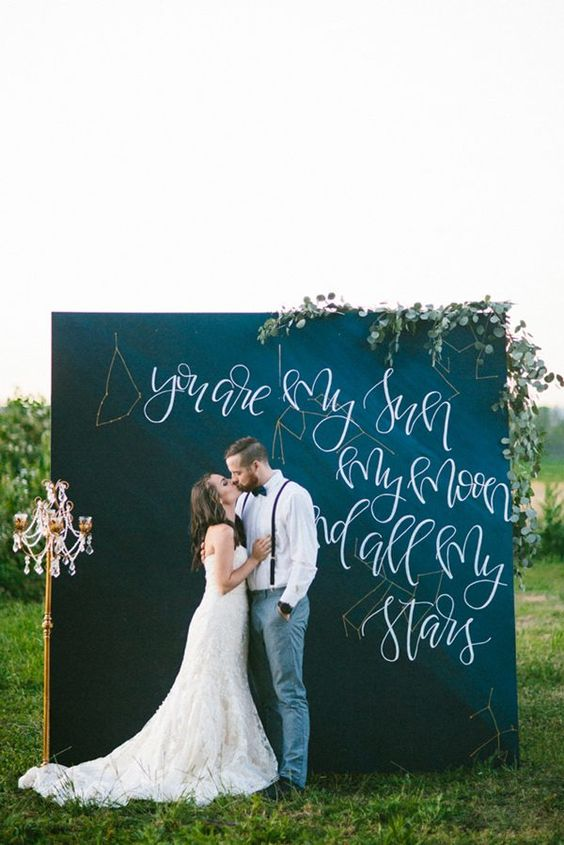 A wedding couple standing outside against a large chalkboard with cursive lettering on in