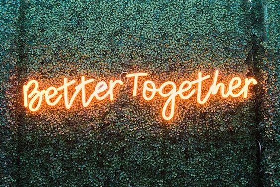 """A neon sign that reads """"better together"""" displayed outside against some greenery"""