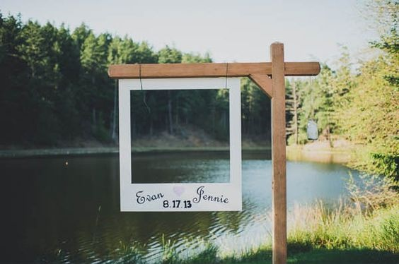 A white Polaroid-style photo frame hanging on a wooden stand with a river in the background
