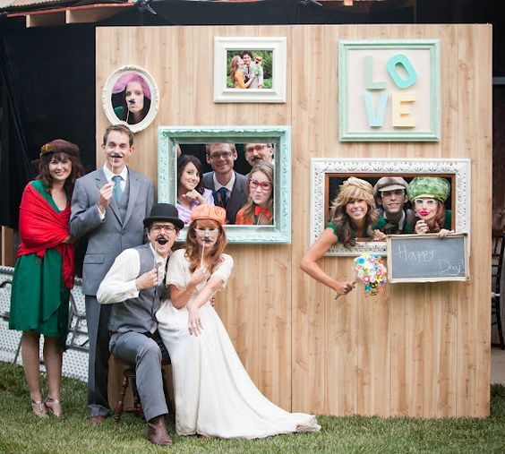 A group of people posing against a photo frame backdrop where the photo frames are empty so people can put their faces in the frames