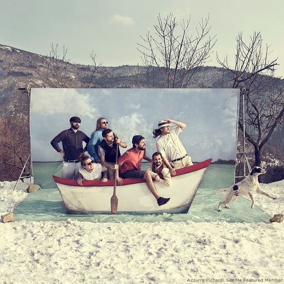 A group of men posing for a funny photo in a stationary row boat set up against a photo backdrop