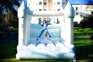 A wedding couple bouncing on a giant bouncy castle outside