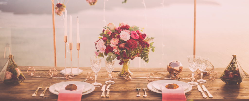 A pink and gold themed table setting display, with plates, cutlery, glasses flowers and hanging baskets