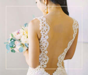 An image of a woman wearing a lacy wedding dress with her back to the camera, holding a bouquet of flowers